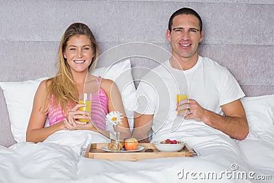 愉快的年轻夫妇吃早餐在床
