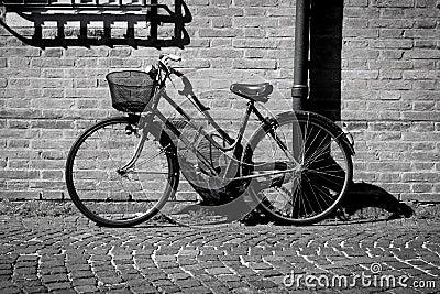 倾斜对在历史的centreof费拉拉的墙壁的意大利老式自行车.图片