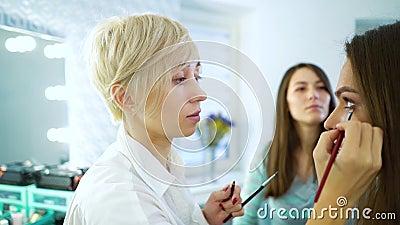 慢动作化妆师和发式专家式样妇女为时装做准备 股票录像