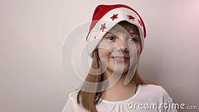 戴着圣诞帽的怪人白人女孩笑着,笑着在白色背景中 股票视频