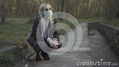 戴着面罩和太阳镜的金发小女孩坐在公园的驼背上,和小狗说话 千禧代高加索人 股票录像