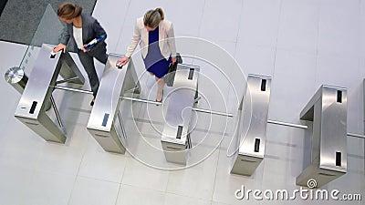 扫描他们的卡片的女实业家在旋转门门 股票录像
