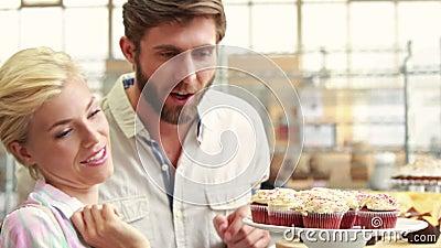 把杯形蛋糕指向的愉快的夫妇餐馆 股票录像