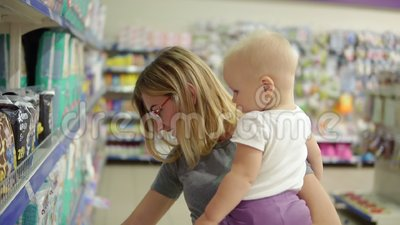 抱她的她的胳膊的玻璃的年轻可爱的母亲孩子,当选择在架子的尿布在时 股票录像