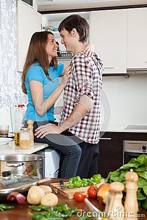 拥抱在厨房里的年轻夫妇图片