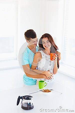 喝与她的丈夫的微笑的年轻美丽的妇女咖啡拥抱她从后面在厨房里.图片