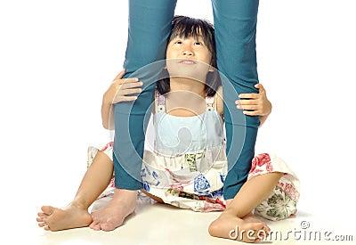 拥抱母亲的腿和查寻她的白色背景的亚裔小女孩母亲.