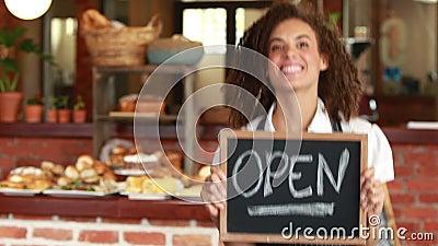 拿着一块开放牌的微笑的barista 影视素材