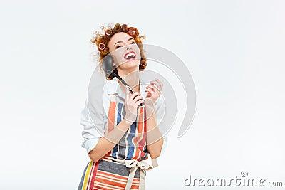 有卷发的笑的红头发人主妇在摆在与汤杓子的围裙隔绝在白色背景.图片