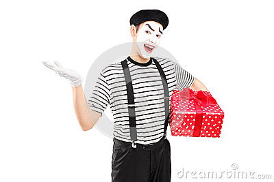 拿着礼物盒和打手势用他的手的男性笑剧艺术家