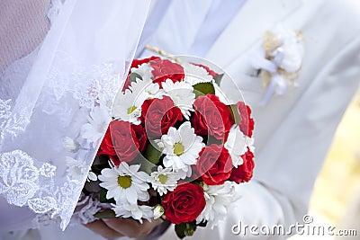 拿着红色玫瑰的美丽的花束新娘婚姻