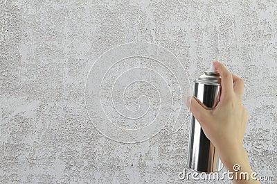 拿着在空白的混凝土墙前面的人的手一个街道画喷壶.图片