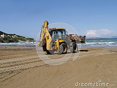挖掘机的铁锹清洁海滩 编辑类库存照片