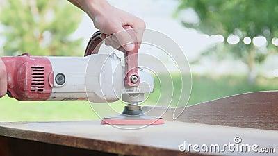 擦亮与一台电动砂光机的木匠一张木桌在车间特写镜头 股票录像