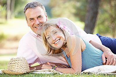 放松在夏天庭院里的高级夫妇