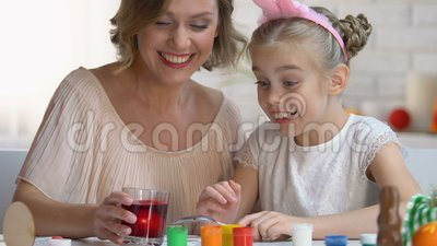 放鸡蛋的滑稽的头饰带的女孩入红色食用色素,复活节传统 股票视频