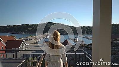 敬佩在旅馆大阳台的年轻红发妇女海视图在海岸在北欧 股票视频