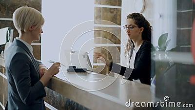 旅馆招待会付帐的女实业家客人不接触的付款信用卡片技术和谈话与 影视素材