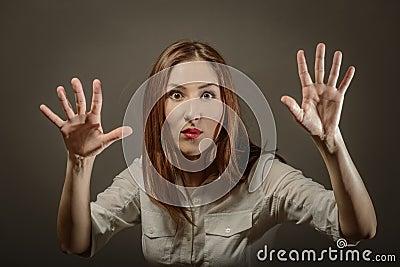 做五次的惊奇少妇特写镜头画象签署与手手指的姿态在灰色背景.