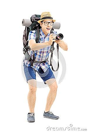 有拍与照相机的背包的男性游人一张照片