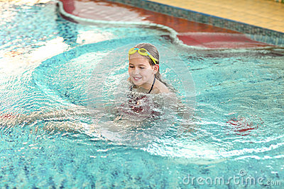 有风镜的愉快的女孩在游泳池