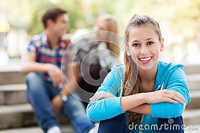有朋友的微笑的妇女在背景中