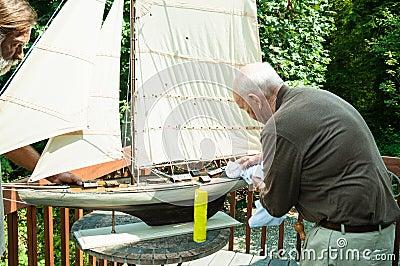 有模型小船的有效的年长人和儿子