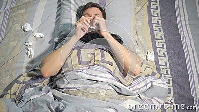 有流感的不适的人和鼻涕抹他的鼻子与组织,当在家时说谎在长沙发 股票录像