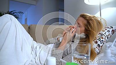 有热病和流鼻水的一名妇女使用鼻孔喷射并且响亮地打喷嚏 移动式摄影车 股票视频