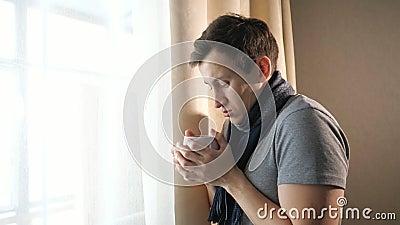 有热的饮料的病的人在窗口附近 股票视频