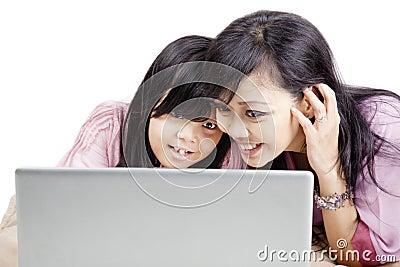 有膝上型计算机的愉快的母亲和女儿