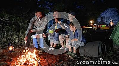 有childs的父母烤在营火的蛋白软糖到森林地,在火的愉快的家庭油炸物蛋白软糖 股票录像