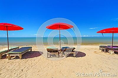 有deckchair的红色遮阳伞在热带海滩