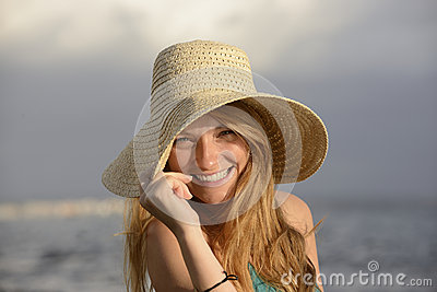 有sunhat的白肤金发的妇女在海滩