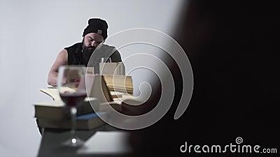 残酷有胡子的男人和年轻无法认出的妇女黑色衣服的在长的桌上与许多书坐它 股票视频