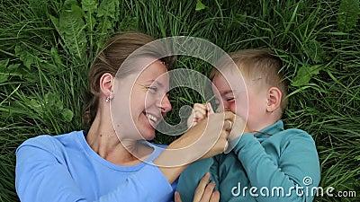 母亲和儿子乐趣消遣  妈妈和三岁的儿子谎言在草和获得乐趣 股票视频
