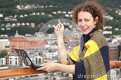 毯子的女孩与在甲板的膝上型计算机