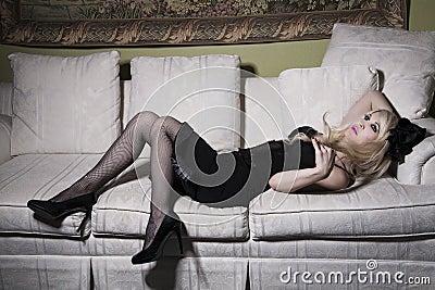 沙发的白肤金发的妇女