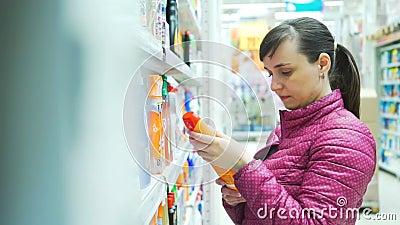 洗涤剂的妇女购物在超级市场 股票录像