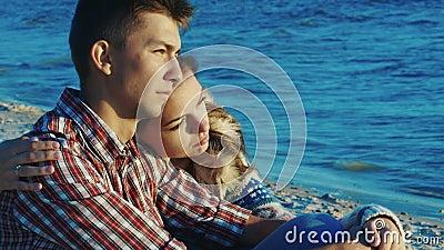 浪漫的情侣在沙滩上放松,她紧紧抱住那个男人 秋天晴多风 股票视频