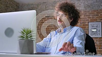 浮现在脑海书呆子程序员的想法与容量卷发的,研究膝上型计算机和坐在现代办公室 影视素材