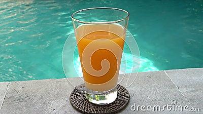 热带度假村游泳池边缘的水中一杯果汁 股票录像