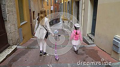 照顾和她的沿老欧洲城市的狭窄的街道的女儿步行 股票视频