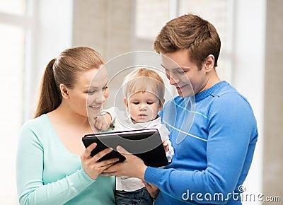父母和可爱的婴孩有片剂个人计算机的
