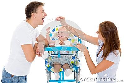 年轻父母饲料婴孩。