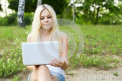 特写镜头使用年轻人的女孩膝上型计&#