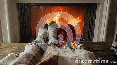 特写镜头夫妇慢动作录影在爱的在说谎在毯子下的温暖的袜子在有灼烧的壁炉的客厅 影视素材