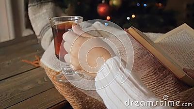 特写镜头妇女阅读书和饮用的茶慢动作英尺长度在沙发nex对发光的圣诞树 影视素材