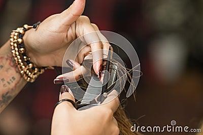 特写镜头有纹身花刺切口深色的头发的美发师手使用剪刀和黑coam.