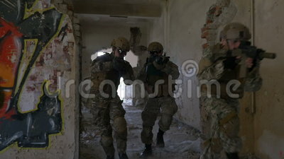 特种部队跑和传播通过一个大厦的废墟的军队小队的慢动作在军事演习的 股票视频